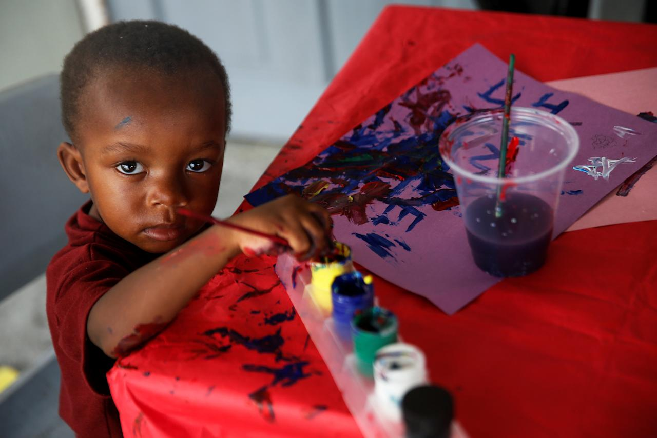 <p>A Barbuda boy paints in a shelter in Antigua for those forced to leave the island just after a month after Hurricane Irma struck the Caribbean islands of Antigua and Barbuda, October 7, 2017. REUTERS/Shannon Stapleton </p>