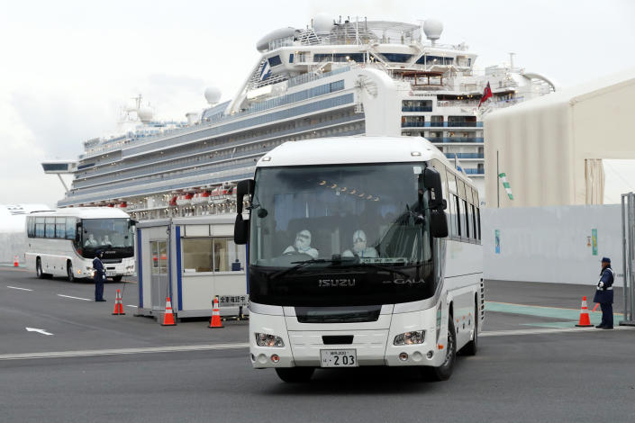 A bus carrying passengers from the quarantined Diamond Princess cruise ship leaves a port in Yokohama, Japan