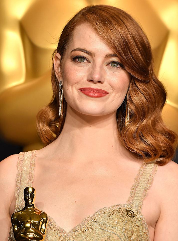 <p>If you're a redhead like Emma Stone, side-swept waves paired with a copper-toned lipstick are the perfect combination to try. (Photo: Getty Images) </p>