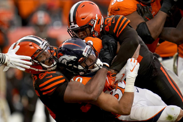 FILE - In this Nov. 3, 2019, file photo, Denver Broncos running back Phillip Lindsay, center, is tackled by Cleveland Browns defensive tackle Sheldon Richardson, left, during the second half of NFL football game, in Denver. While Myles Garrett serves his indefinite NFL suspension for hitting Pittsburgh quarterback Mason Rudolph over the head with a swung helmet, the Cleveland Browns have to find someone to hold down the star defensive ends spot. (AP Photo/Jack Dempsey)