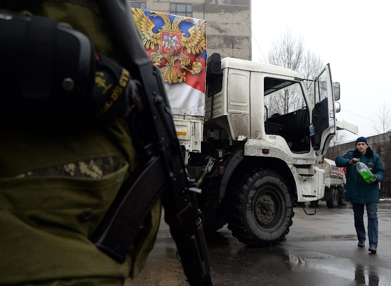 """An armed fighter (L) of the self-proclaimed """"People's Republic of Donetsk"""" stands guard by a Russian convoy"""