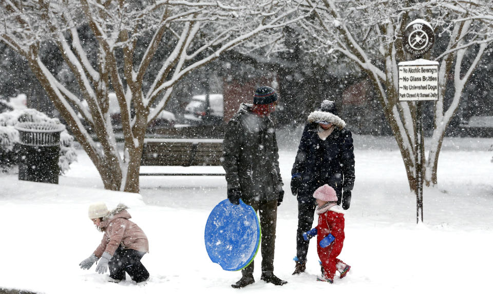Aaron Savage and wife Bonnie Wright watch as their children Mabel Savage, 4, left, and Sadie Savage, 2, play in the snow during a winter storm on Sunday, Jan. 31, 2021, in Richmond, Va. (Joe Mahoney/Richmond Times-Dispatch via AP)