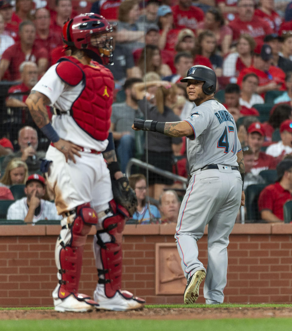 Miami Marlins' Harold Ramirez, right, looks back at St. Louis Cardinals catcher Yadier Molina, left, after Ramirez scored during the sixth inning of a baseball game Thursday, June 20, 2019, in St. Louis. (AP Photo/L.G. Patterson)