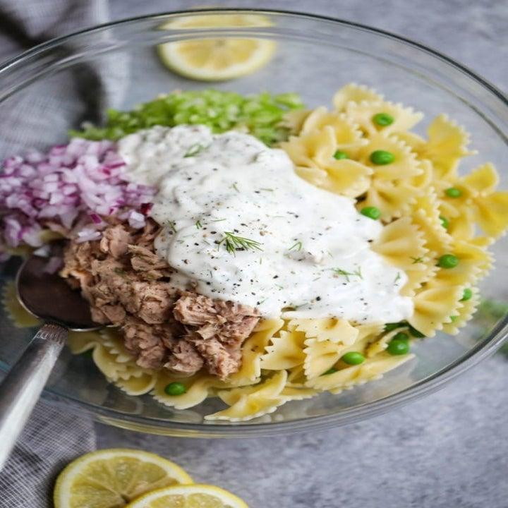 Pasta, canned tuna, peas, onion, and mayo in a mixing bowl.