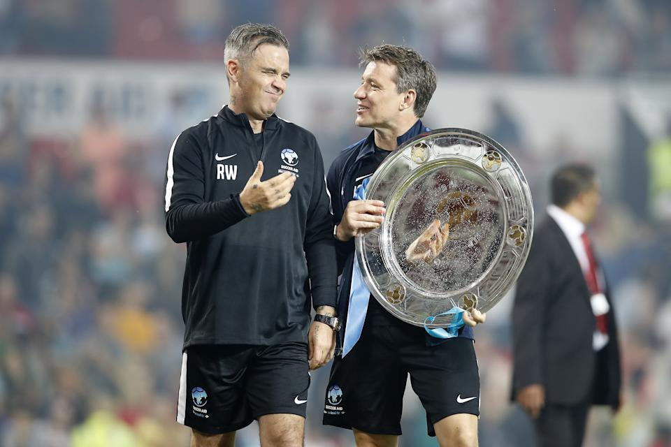 England's Robbie Williams (left) and Ben Shephard (right) with the trophy after the final whistle during the UNICEF Soccer Aid match at Old Trafford, Manchester. (Photo by Martin Rickett/PA Images via Getty Images)