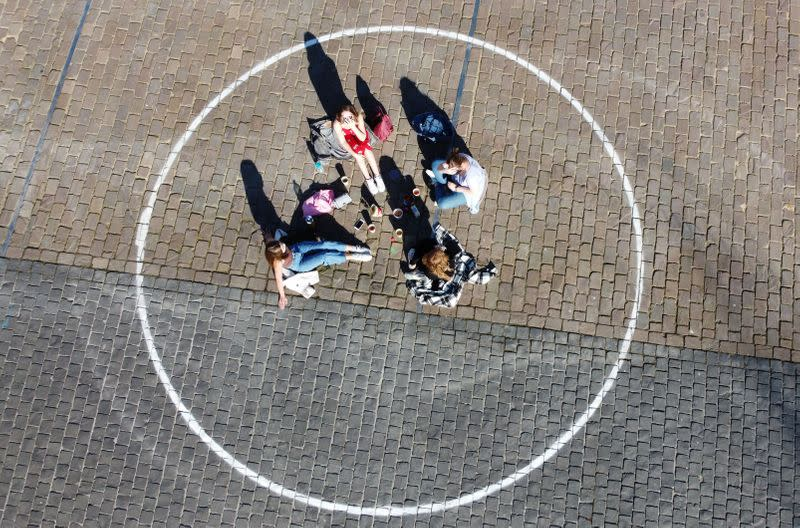 People relax inside social distancing circles in Ghent