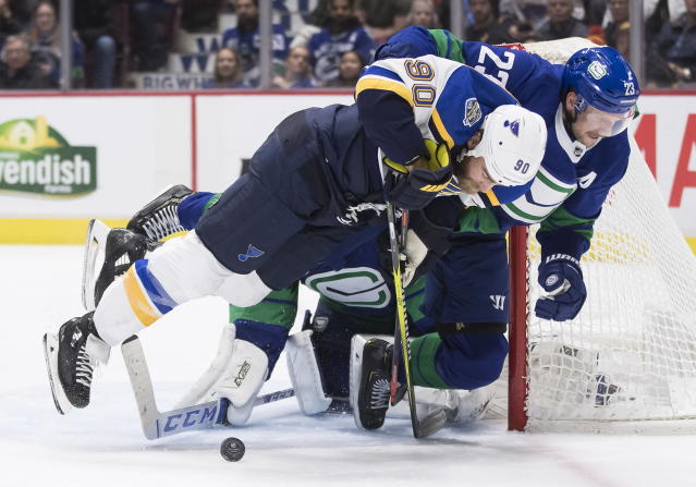 Vancouver Canucks' Alexander Edler (23), of Sweden, hauls down St. Louis Blues' Ryan O'Reilly (90), in front of goalie Jacob Markstrom, back, of Sweden, during the third period of an NHL hockey game Tuesday, Nov. 5, 2019, in Vancouver, British Columbia. (Darryl Dyck/The Canadian Press via AP)