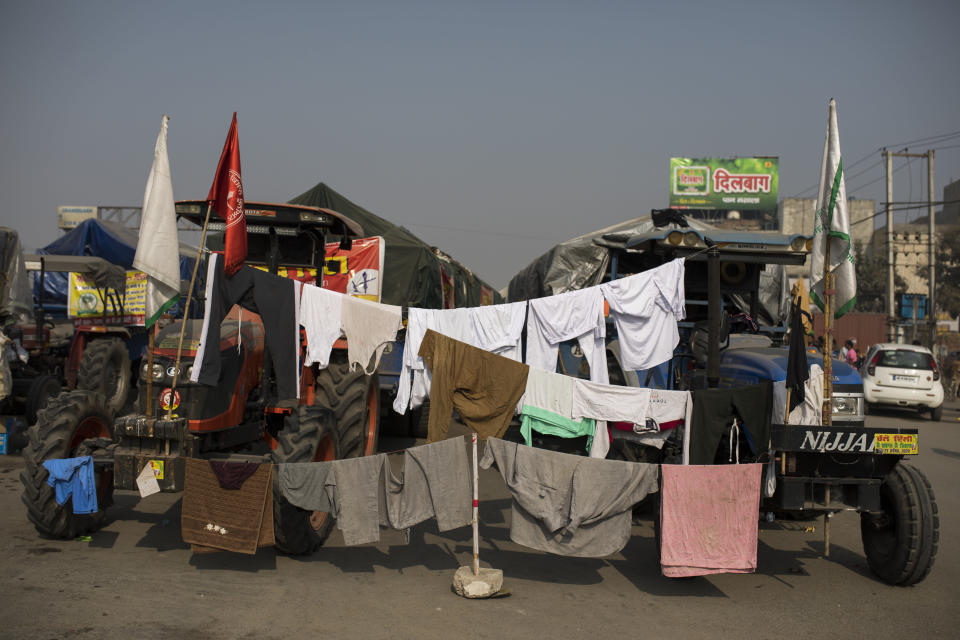 "Clothes of protesting farmers hang to dry on lines attached to their tractors as they block a major highway protesting new farming laws they say will result in exploitation by corporations, eventually rendering them landless, at the Delhi-Haryana state border, India, Tuesday, Dec. 1, 2020. The busy, nonstop, arterial highways that connect most northern Indian towns to this city of 29 million people, now beat to the rhythm of never-heard-before cries of ""Inquilab Zindabad"" (""Long live the revolution""). Tens and thousands of farmers, with colorful distinctive turbans and long, flowing beards, have descended upon its borders where they commandeer wide swathes of roads. (AP Photo/Altaf Qadri)"