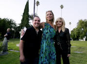 Sculptor Caroline PM Jones, center, poses with the late actor Burt Reynolds' son Quinton, left, and his former wife Loni Anderson during a ceremony to unveil her sculpture of Reynolds at Hollywood Forever Cemetery, Monday, Sept. 20, 2021, in Los Angeles. Reynolds died in 2018 at the age of 82. (AP Photo/Chris Pizzello)