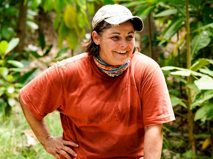 Elaine Stott on Survivor wearing a red shirt and hat in front of a forest