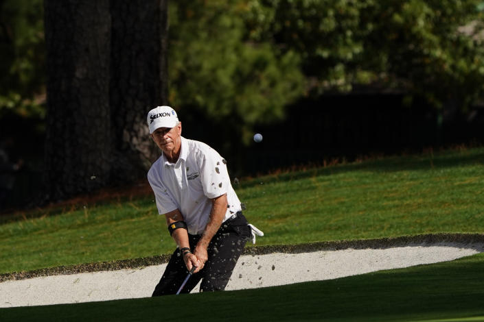 Larry Mize chips out of a bunker on the seventh hole during the first round of the Masters golf tournament Thursday, Nov. 12, 2020, in Augusta, Ga. (AP Photo/Matt Slocum)