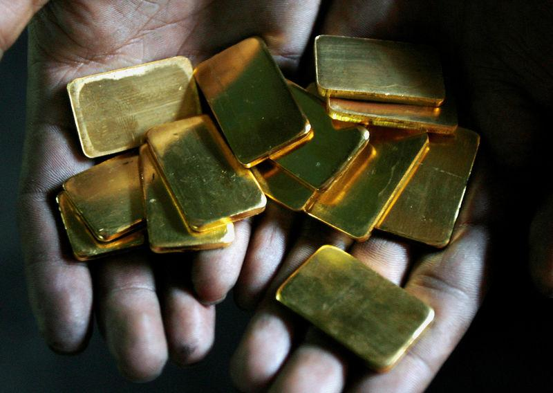 FILE PHOTO: A worker shows gold biscuits at a precious metals refinery in Mumbai