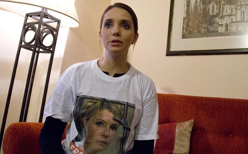 Eugenia Tymoshenko, daughter of jailed Ukrainian politician Yulia Tymoshenko, wears a t-shirt with her mothers photograph on it as she speaks with the Associated Press during an interview on the sidelines of an Eastern Partnership Summit in Vilnius on Thursday, Nov. 28, 2013. European Union leaders meet Thursday and Friday for a summit that is set to be overshadowed by a power struggle with Russia for influence in post-Soviet states. (AP Photo/Virginia Mayo)