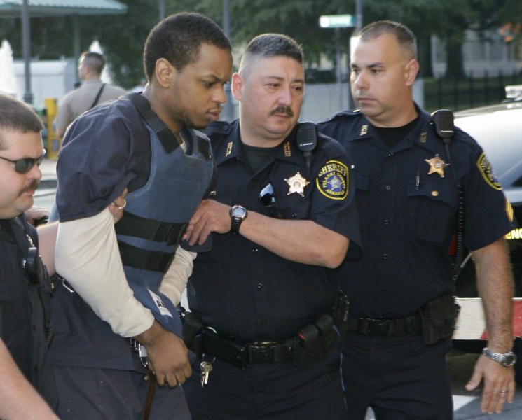 """FILE - In this Thursday, July 21, 2011 file photo, Abdulhakim Muhammad, second from left, is escorted to the Pulaski County Courthouse in Little Rock, Ark., for his trial for the June 1, 2009, shooting death of Pvt. William Long and the wounding of the second soldier outside the recruiting office in west Little Rock. Muhammad, who changed his name from Carlos Bledsoe when he converted to Islam, grew up in the Memphis, Tenn., area and then traveled to Yemen, returning to the U.S. in 2008. Since the shooting, in a two-page letter to the judge presiding over his case, Muhammad has described himself as a soldier in al-Qaida in the Arabian Peninsula and called the shooting """"a jihadi attack.""""(AP Photo/Danny Johnston, File)"""