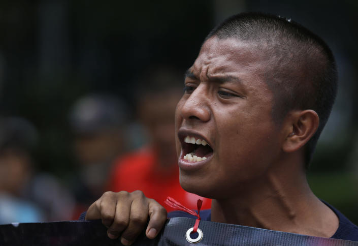 A demonstrator chants slogans calling for justice in the case of 43 missing students from the Isidro Burgos rural teachers college, as he joins a march by residents protesting the construction of a new airport, in Mexico City, Thursday, Aug. 23, 2018. Demonstrators marched to protest a $15.7-billion airport project that threatens a decades-old effort to restore lakes that originally covered the valley. (AP Photo/Marco Ugarte)