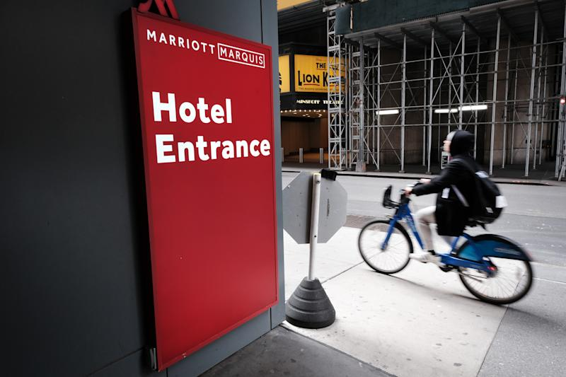 NEW YORK, NY - MARCH 22: A person rides a bike past the Marriott hotel in Times Square as much of the city is void of cars and pedestrians over fears of spreading the coronavirus on March 22, 2020 in New York City. Marriott has announced furlough thousands of workers at its properties throughout the country. Across the country schools, businesses and places of work have either been shut down or are restricting hours of operation as health officials try to slow the spread of COVID-19. (Photo by Spencer Platt/Getty Images)