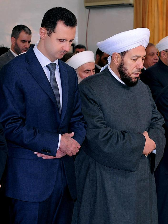 FILE - In this Feb. 5, 2012 photo released by the Syrian official news agency SANA, Syrian President Bashar Assad, left, prays next to the Syrian grand mufti Ahmad Hassoun, right, during a ceremony marking the birth of Islam's Prophet Mohammad, at al-Rawda mosque, in Damascus, Syria. Hassoun's appeal for men to join the army raises the question of whether President Bashar Assad is running out of soldiers and prompts a pro-government newspaper to declare the military can battle insurgents for years to come. The civil war has eroded one of the Arab world's biggest armies, and pro-Assad militiamen are increasingly filling in for troops. (AP Photo/SANA, File)