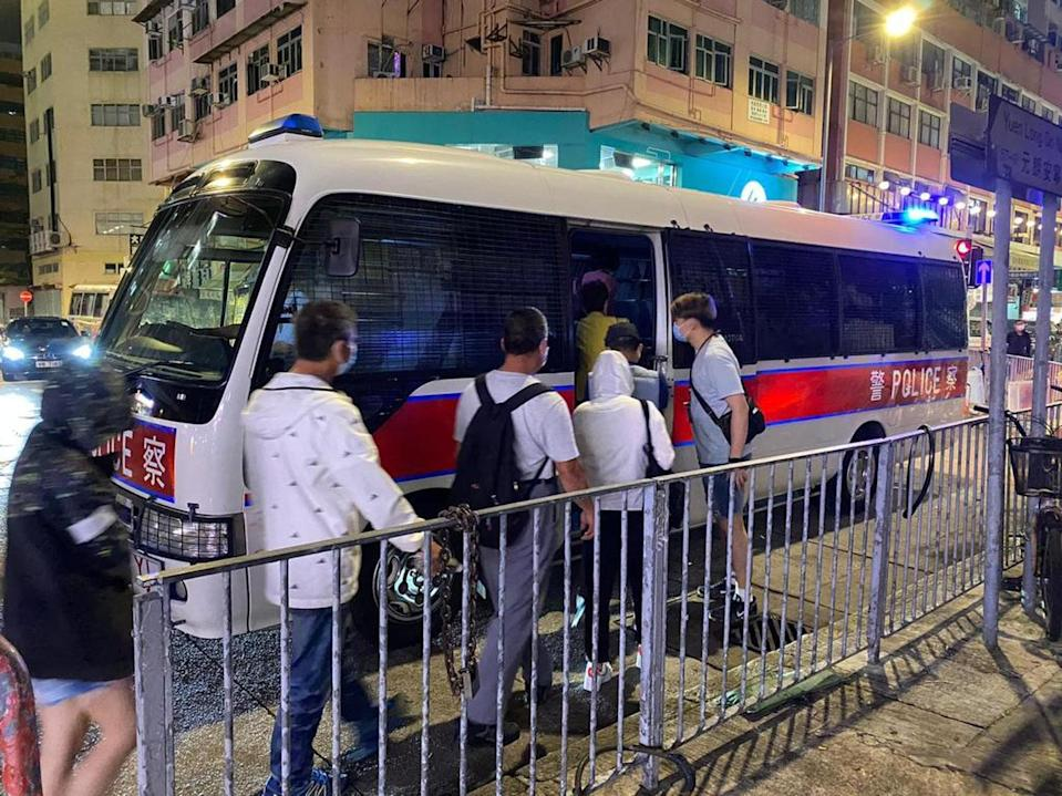 Suspects are escorted into a police van after they were arrested in a raid on a separate gambling den in Yuen Long on Sunday. Photo: Handout