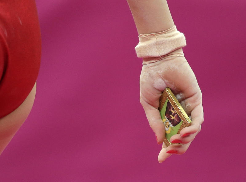 Russian gymnast Kseniia Afanaseva holds a portrait of an Orthodox Saint after her performance during the artistic gymnastics women's floor exercise final at the 2012 Summer Olympics, Tuesday Aug. 7, 2012, in London. Afanaseva placed the portrait near the mat prior to her performance. (AP Photo/Gregory Bull)
