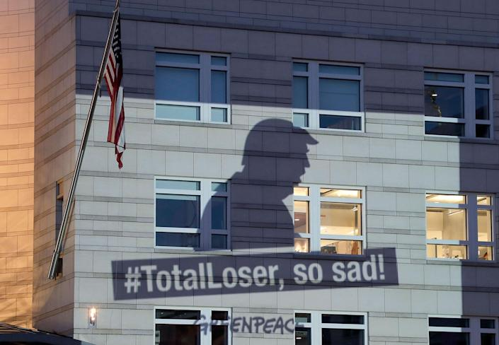 <p>A Greenpeace banner showing President Donald Trump and the slogan '#TotalLoser, so sad!' is projected onto the facade of the U.S. Embassy in Berlin, Germany, Friday, June 2, 2017. (AP Photo/Michael Sohn) </p>