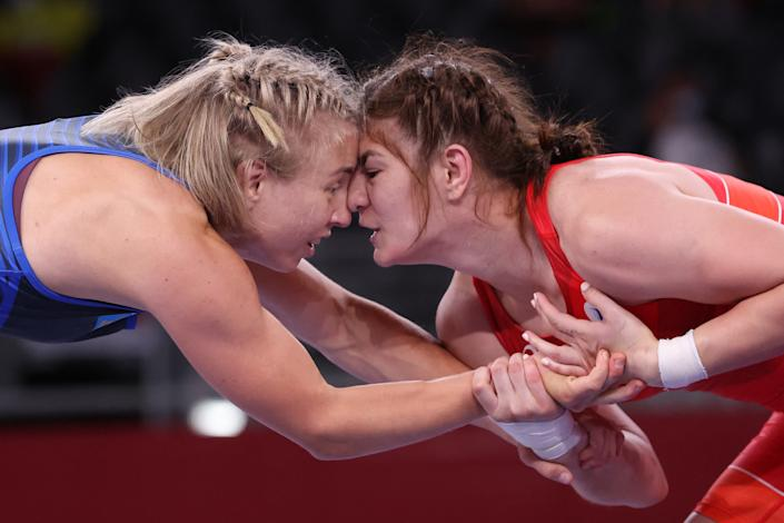 <p>Russia's Liubov Ovcharova (red) wrestles Sweden's Henna Katarina Johansson in their women's freestyle 62kg wrestling repechage match during the Tokyo 2020 Olympic Games at the Makuhari Messe in Tokyo on August 4, 2021. (Photo by Jack GUEZ / AFP)</p>