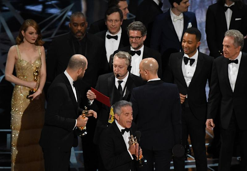 """""""La La Land"""" producer Jordan Horowitz (2L) speaks to stage manager Gary Natoli (C), reading the winners card, after """"La La Land"""" mistakenly won the best picture instead of """"Moonlight"""" at the 89th Oscars on February 26, 2017"""