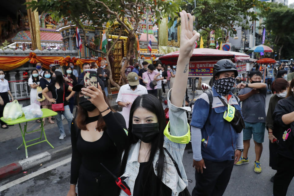 Pro-democracy demonstrators flash a three-finger salute of defiance during a protest rally in the Silom business district of Bangkok, Thailand, Thursday, Oct. 29, 2020. The protesters continue to gather Thursday with their three main demands of Prime Minister Prayuth Chan-ocha's resignation, changes to a constitution that was drafted under military rule and reforms to the constitutional monarchy. (AP Photo/Gemunu Amarasinghe)