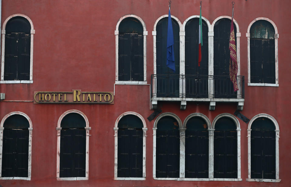 A view of a hotel with windows closed in Venice, Italy, Saturday, Jan. 30, 2021. Gondolas and other vessels are moored instead of preparing for Carnival's popular boat parade in the lagoon. Alleys are eerily empty. Venetians and the city's few visitors stroll must be masked in public places, indoors and out, under a nationwide mandate.(AP Photo/Antonio Calanni)