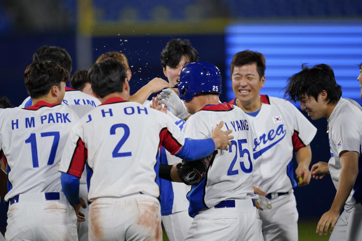 South Korea's Euiji Yang celebrates with teammates after being hit by pitch to walk in the winning run in the tenth inning of a baseball game against Israel at the 2020 Summer Olympics, Thursday, July 29, 2021, in Yokohama, Japan. South Korea won 6-5.(AP Photo/Sue Ogrocki)