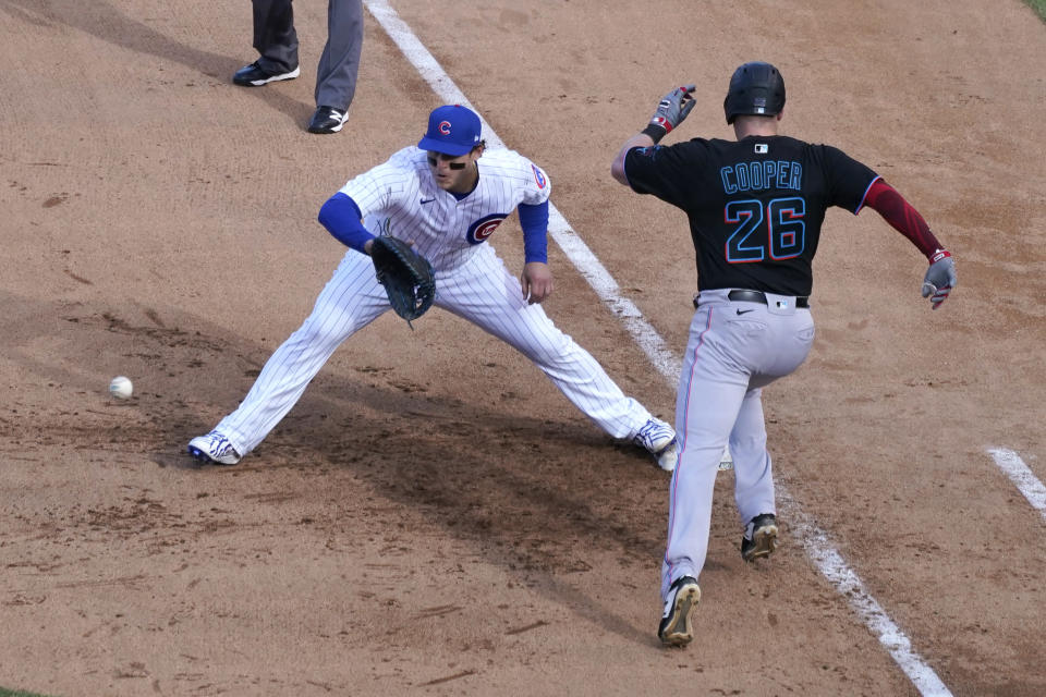 Miami Marlins' Garrett Cooper (26) grounds out as Chicago Cubs first baseman Anthony Rizzo handles the throw during the ninth inning in Game 2 of a National League wild-card baseball series Friday, Oct. 2, 2020, in Chicago. (AP Photo/Nam Y. Huh)