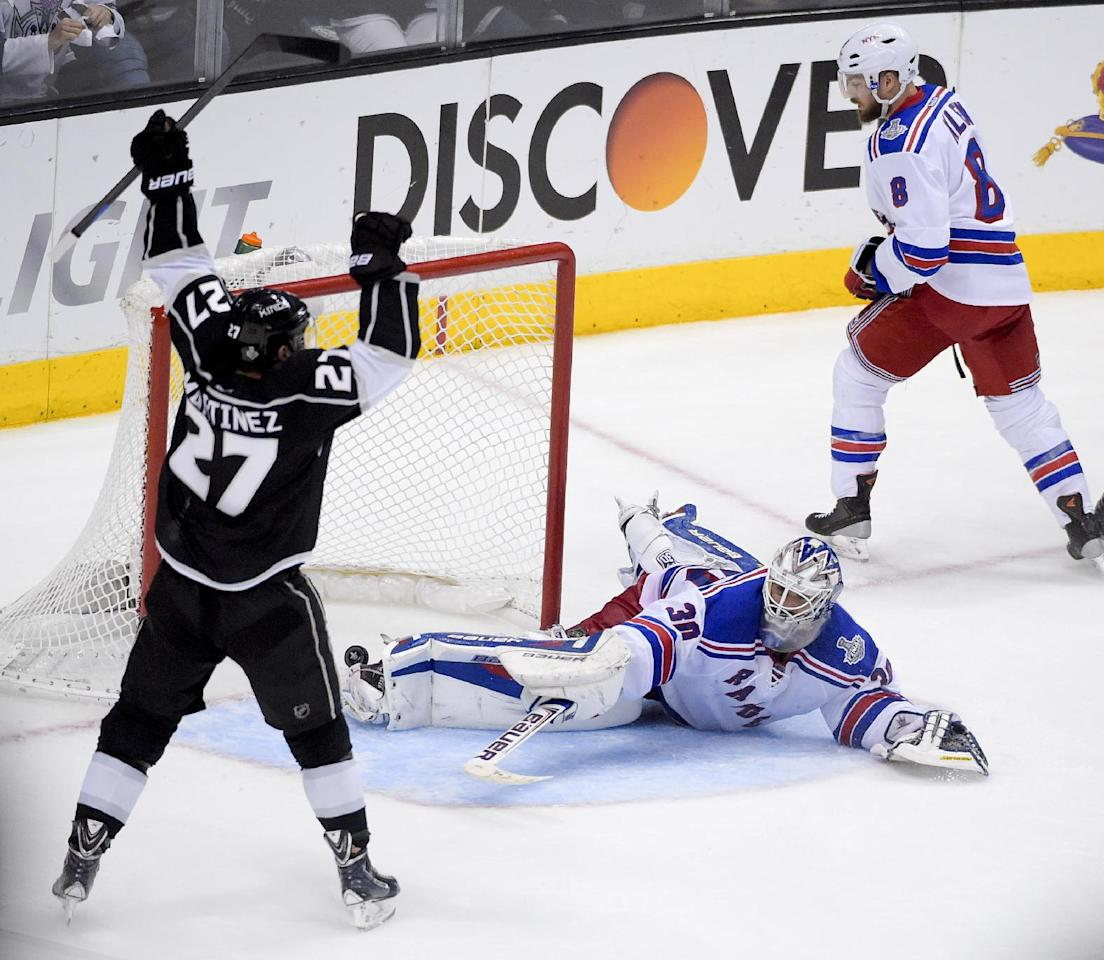 Los Angeles Kings defenseman Alec Martinez, left, celebrates after scoring  the winning goal past New York Rangers goalie Henrik Lundqvist, of Sweden, during the second overtime period in Game 5 of an NHL hockey Stanley Cup finals, Friday, June 13, 2014, in Los Angeles.  (AP Photo/Mark J. Terrill)
