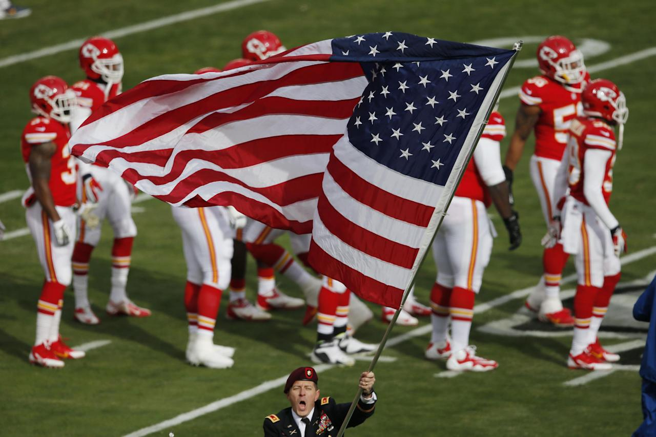 A soldier waves an American flag before an NFL football game between the San Diego Chargers and Kansas City Chiefs at Arrowhead Stadium in Kansas City, Mo., Sunday, Nov. 24, 2013. It was military appreciation day at Arrowhead. (AP Photo/Orlin Wagner)