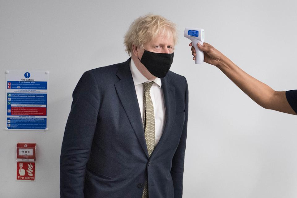 Prime Minister Boris Johnson has his temperature taken during a visit to view the vaccination programme at Chase Farm Hospital in north London, part of the Royal Free London NHS Foundation Trust. The NHS is ramping up its vaccination programme with 530,000 doses of the newly approved Oxford/AstraZeneca Covid-19 vaccine jab available for rollout across the UK.