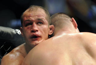 Junior dos Santos grapples with Cain Velasquez during their grueling fight. (AP)