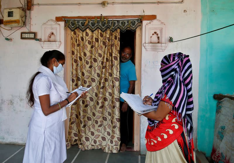 FILE PHOTO: Health workers collect personal data from a man as they prepare a list during a door-to-door survey on the outskirts of Ahmedabad