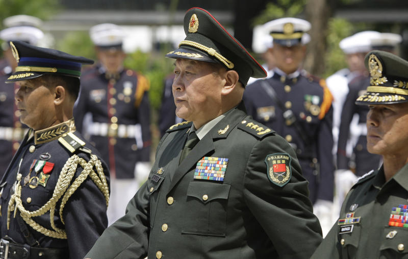 Chinese Defense Minister Liang Guanglie, center, walks during departure honors at the Defense Headquarters where he met his Philippine counterpart Voltaire Gazmin in suburban Quezon City, north of Manila, Philippines on Monday May 23, 2011. Guanglie's visit comes amid renewed tension over the disputed Spratly Islands, which are claimed by China, the Philippines and four other Asian countries and territories. Washington has expressed concerns that the disputes could hamper access to one of the world's busiest commercial sea lanes. (AP Photo/Aaron Favila)