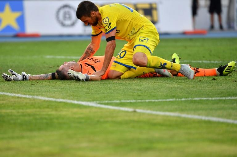 Chievo's Serbian defender Nenad Tomovic tends to goalkeeper Stefano Sorrentino after he was injured