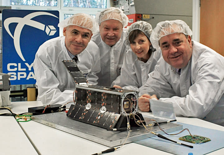 Officials in Glasgow, Scotland, pose in this recent photo with a satellite that will carry artwork created by Los Angeles artists Jon Gibson and Amanda White, not shown, in British company Clyde Space facility in Glasgow. Posing from left are Craig Clark of Clyde Space, Serkey Krutikov, consul general of the Russian Federation in Edinburgh, Lena Wilson, Scottish Enterprise chief executive, and Scotland's First Minster Alex Salmond. The artists believe their work, not visible in this photo, will be the first work of art launched into space, etched into the side of a satellite that Clyde Space is scheduled to send into orbit on Oct. 29 aboard a Soyuz rocket to be launched from Kazakhstan. (AP Photo/Scottish Government Press Office)
