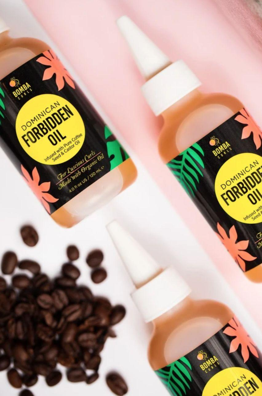 """It'sinfused with pure coffee seed and castor oil to moisturize your hair and scalp, while promoting hair growth and making your strands look glossier.<a href=""""https://go.skimresources.com?id=38395X987171&xs=1&url=https%3A%2F%2Fbombacurls.com%2Fcollections%2Fall-products-excluding-route%2Fproducts%2Fdominican-forbidden-oil&xcust=HPBeautyGifts60884d2de4b0b9042d8b22ef"""" target=""""_blank"""" rel=""""nofollow noopener noreferrer"""" data-skimlinks-tracking=""""5876069