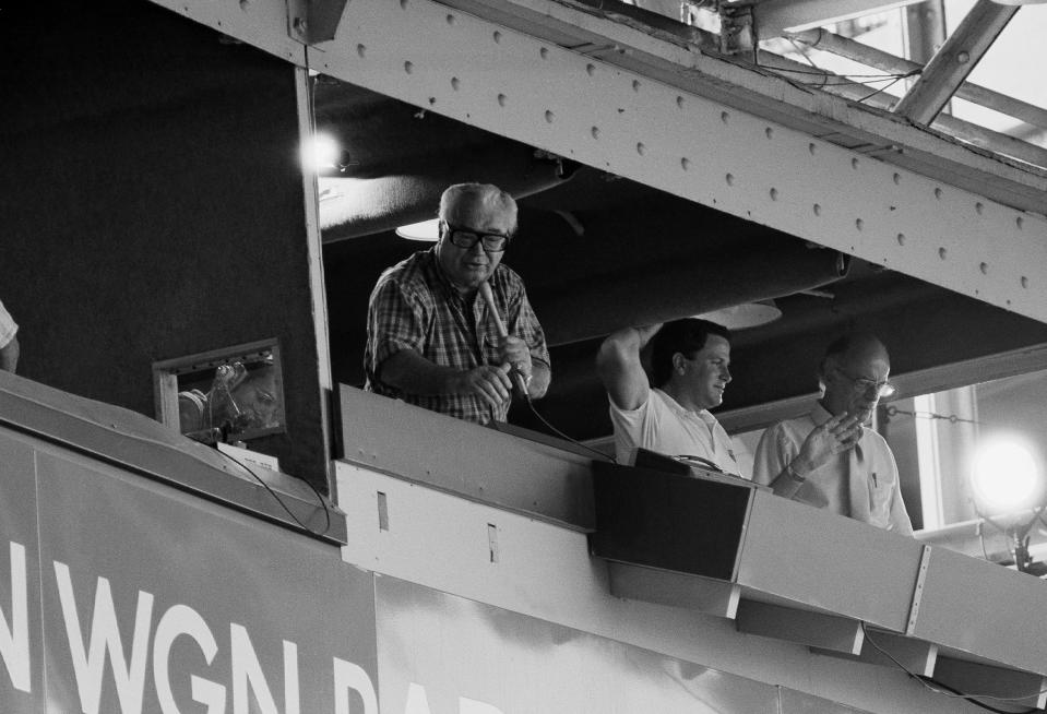 """Harry Caray leans out of his WGN broadcast booth at Chicago's Wrigley Field during the seventh inning stretch of a recent Chicago Cubs baseball game, to lead fans in a rousing verse of """"Take me out to the hall game."""" In center is Steve Stone, while right is Jack Rosenberg both of WGN broadcasting, Oct. 6, 1984 in Chicago. (AP Photo/John Swart)"""