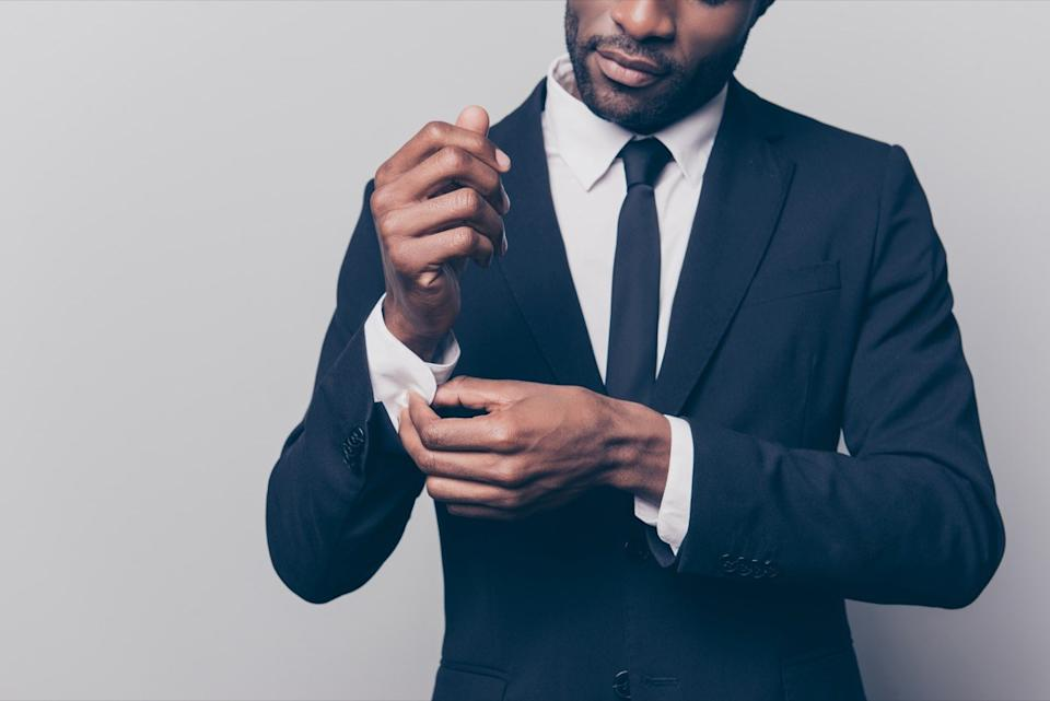 a man buttoning up his suit cuff before going into work