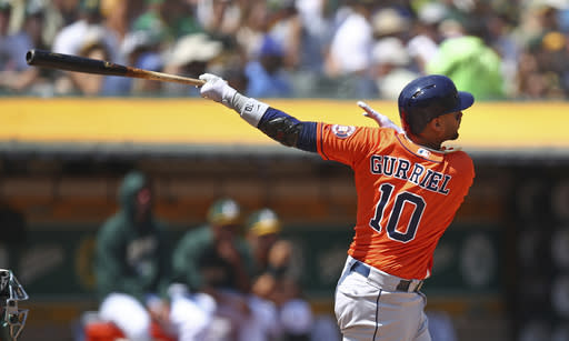 Houston Astros' Yuli Gurriel swings for a three-run home run off Oakland Athletics' Sean Manaea in the third inning of a baseball game Sunday, Aug. 19, 2018, in Oakland, Calif. (AP Photo/Ben Margot)