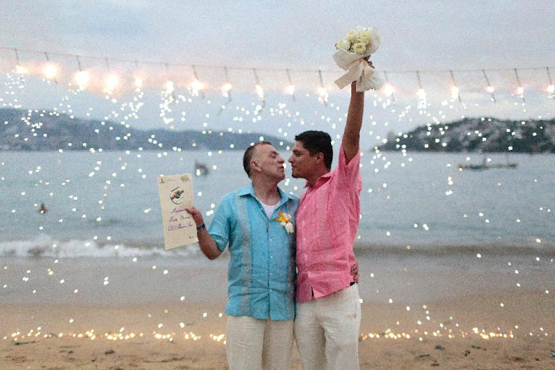 A gay couple takes part in the first same-sex mass wedding in Acapulco, Guerrero State, Mexico on July 10, 2015 (AFP Photo/Pedro Pardo)