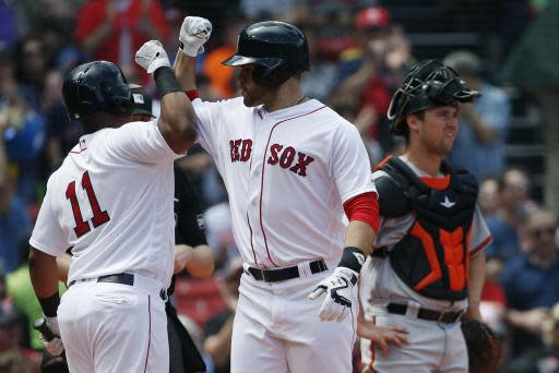 Boston Red Sox's J.D. Martinez, center, celebrates his solo home run with teammate Rafael Devers (11) as Baltimore Orioles' Andrew Susac looks away during the second inning of a baseball game in Boston, Sunday, May 20, 2018. (AP Photo/Michael Dwyer)