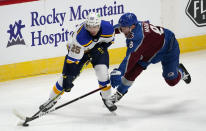 St. Louis Blues center Jordan Kyrou, left, looks to pass the puck as Colorado Avalanche defenseman Cale Makar reaches for it during the first period of an NHL hockey game Wednesday, Jan. 13, 2021, in Denver. (AP Photo/David Zalubowski)