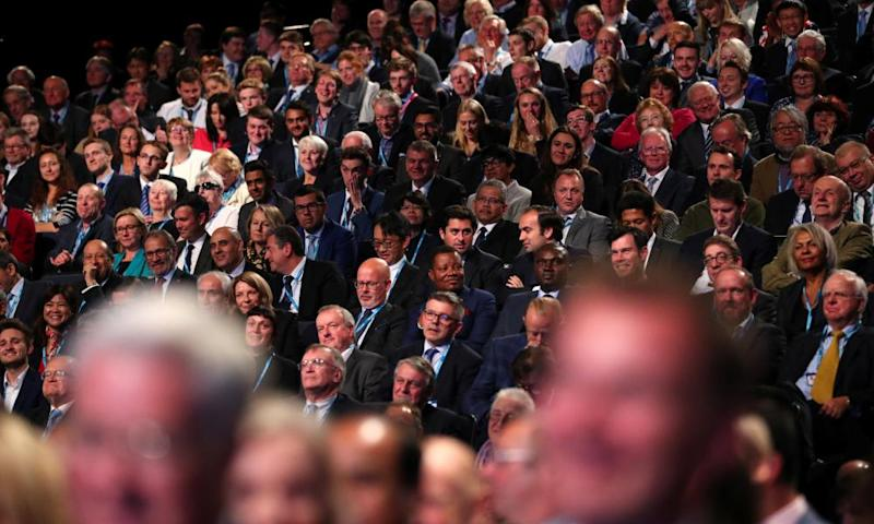 Delegates listen to Britain's Prime Minister Theresa May as she addresses the Conservative Party conference in Manchester.