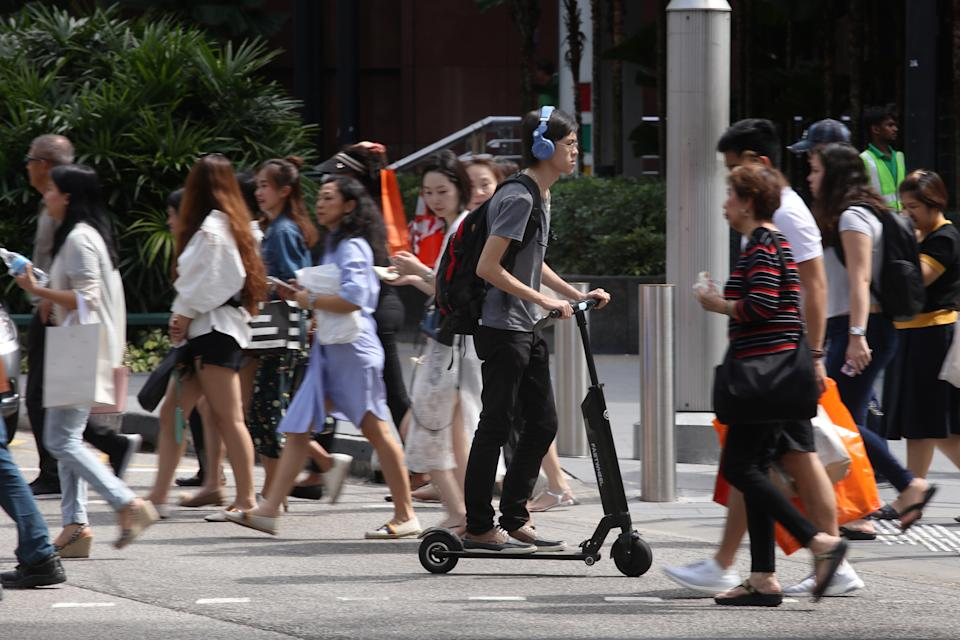A man riding an e-scooter at a pedestrian crossing at Orchard Road. (FILE PHOTO: Yahoo News Singapore)