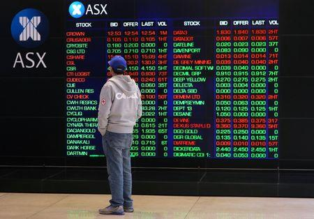 FILE PHOTO - An investor looks at a board displaying stock prices at the Australian Securities Exchange (ASX) in Sydney, Australia