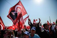 A demonstrator holds a flag picturing Turkish President Recep Tayyip Erdogan among demostrators wawing Turkish national flags and shout slogans on August 7, 2016 in Istanbul during a rally against failed military coup on July 15