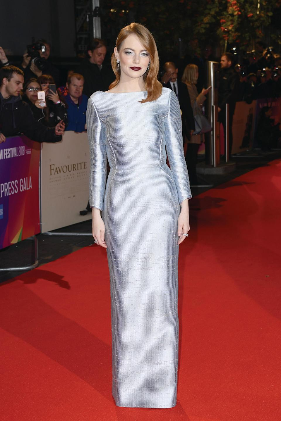 <p>For the 2018 BFI Film Festival, Emma Stone wore a silver long-sleeved Louis Vuitton dress with soft Hollywood curls and a winter-ready lip to finish. <em>[Photo: Getty]</em> </p>